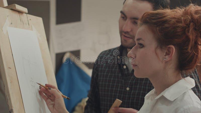 Studet masculino de enseñanza del artista de sexo femenino a pintar en estudio fotos de archivo libres de regalías