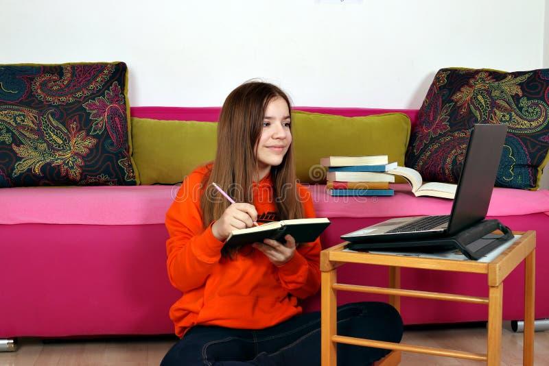 Studi dell'adolescente con un libro e un computer portatile immagini stock libere da diritti