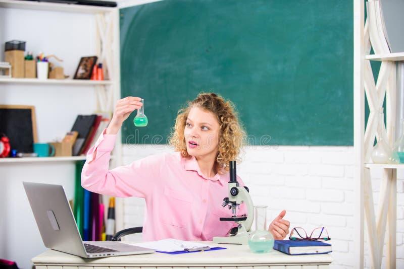 Studi le modifiche molecolari Ragazza dello studente con il computer portatile ed il microscopio Il maestro di scuola continua st fotografia stock