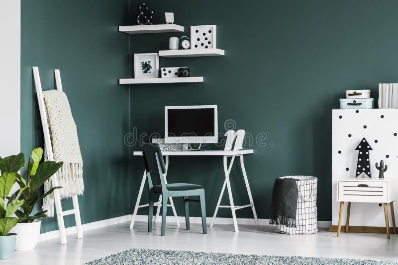 Studi lo spazio per un adolescente in un interno verde scuro della camera da letto con fotografia stock