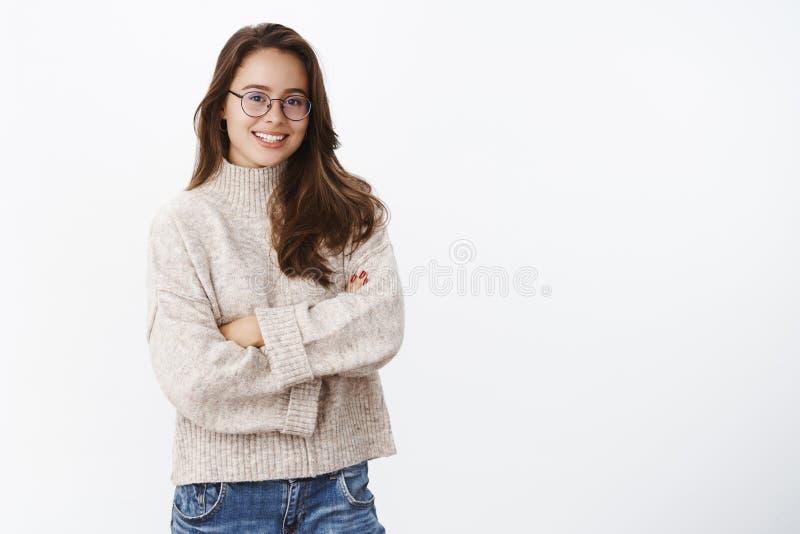 Studi tiró de mujer europea joven creativa y feliz elegante en vidrios con la sonrisa perfecta que celebraba las manos cruzadas e foto de archivo