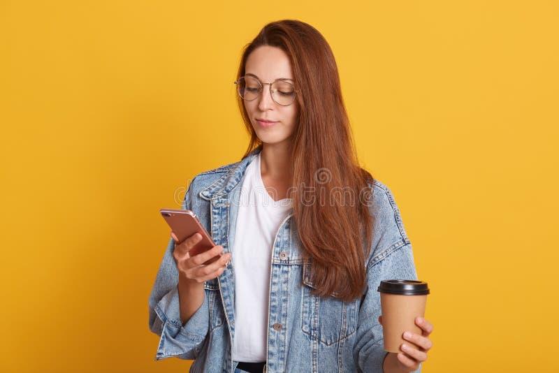 Studia strzał upartej kaukaskiej kobiety czytającej wiadomości na stronie internetowej podczas picia kawy na wynos, trzymając tel zdjęcia royalty free