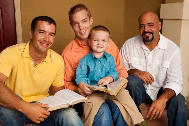 Studie för bibel för grupp för man` s Fader som läser bibeln med hans son fotografering för bildbyråer