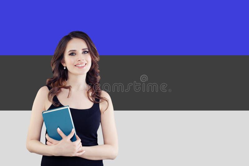 Studie i Estland Lyckad smart kvinna på estonian flaggabakgrund arkivbilder