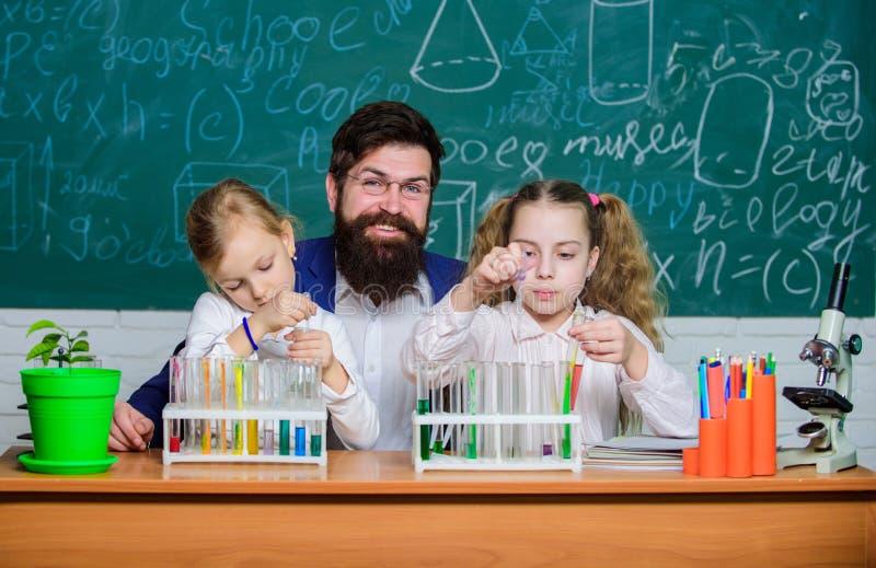 Studie slimmere niet harder Kleine leerlingen die chemie bestuderen Kleine schoolmeisjes die voor biologieexamen bestuderen met p stock afbeelding