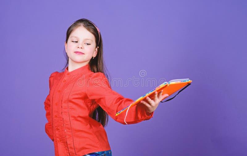 Studieren Sie und erlernen Sie Violetter Hintergrund des M?dchengriff-Buches Kindershowbuch Buchkonzept Kluge Zitate Literaturclu stockfotografie