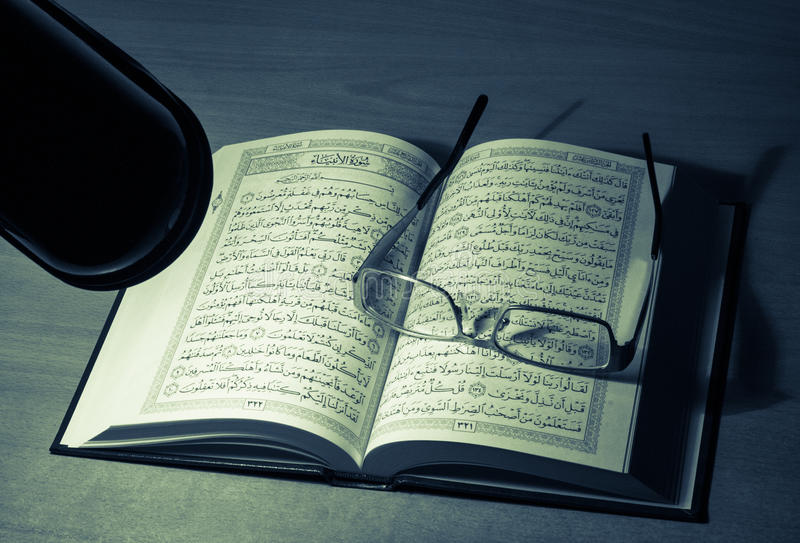 Studieren von Quran nachts hinter Schreibtisch stockfoto