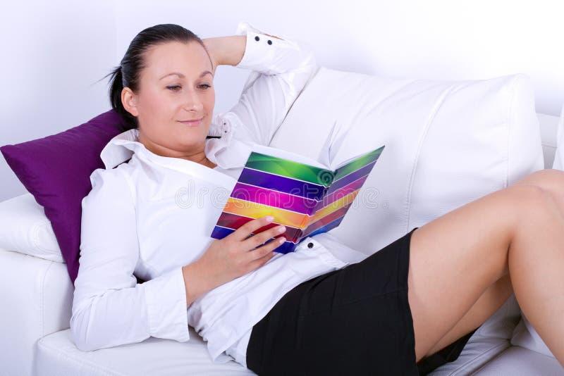 Studierendes Buch des attraktiven Brunette auf weißer Couch