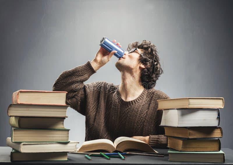 Studierendes und trinkendes Energiegetränk des jungen Mannes stockbilder