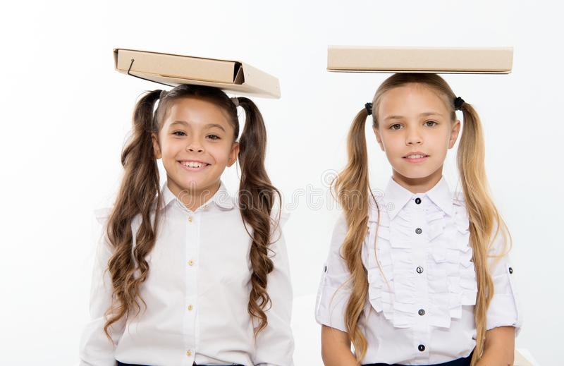 Studies and learning. Happy kids girls keep file folders on head. studies and learning of kids enjoy school day stock images