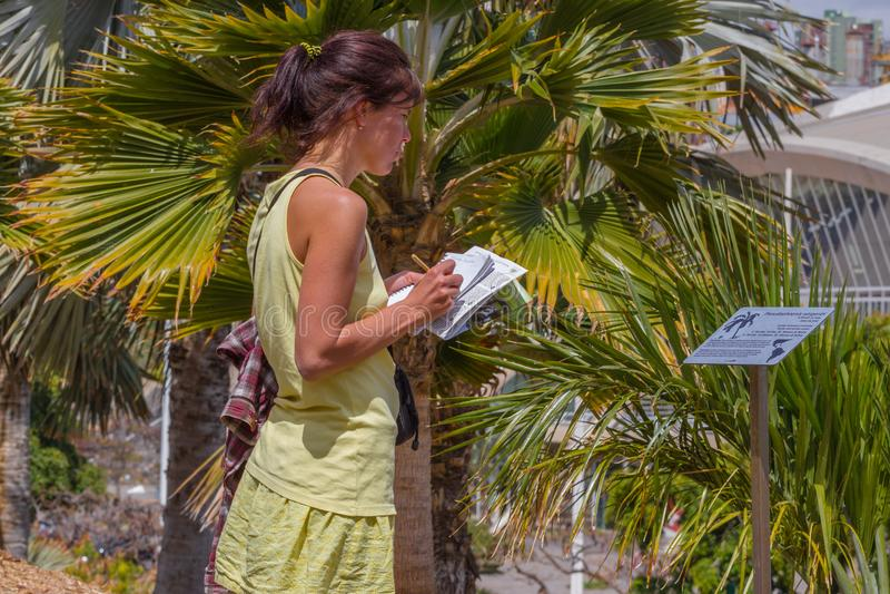 Studing växter för kvinna i botanisk trädgård i tropisk del fotografering för bildbyråer