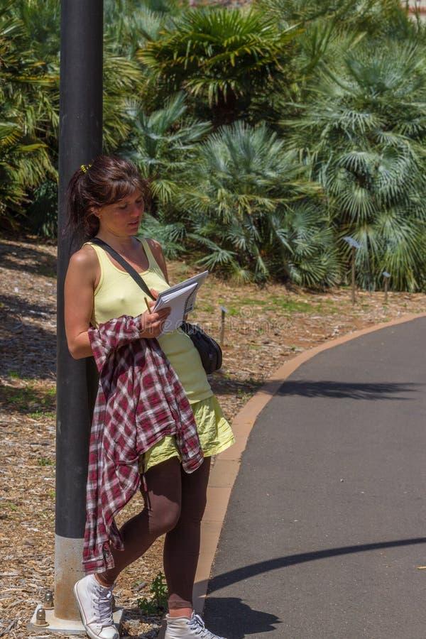 Studing växter för kvinna i botanisk trädgård i tropisk del royaltyfria foton