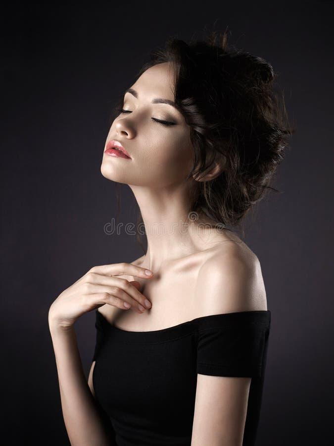 Beautiful woman with elegant hairstyle on black background. Studio art portrait of beautiful woman with elegant hairstyle on black background stock photography