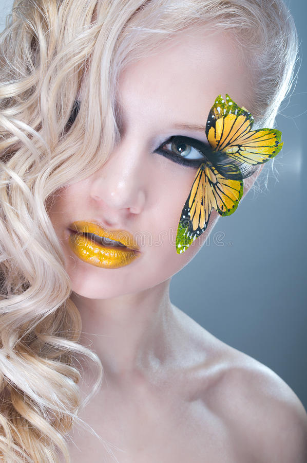 Studio beauty portrait with yellow butterfly. Studio beauty portrait of woman with yellow butterfly stock images