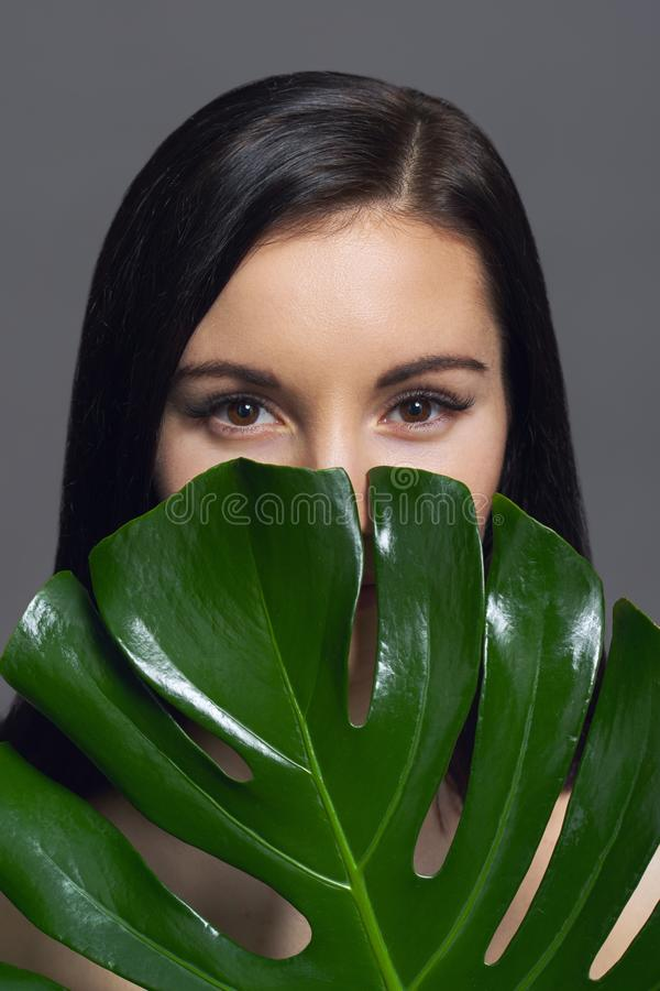 Studio beauty portrait of young brunette with natural make-up perfect skin with green exotic leaf on gray background. Concept of stock photos
