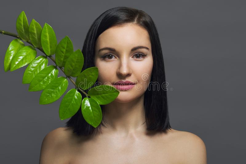 Studio beauty portrait of young brunette with natural make-up perfect skin with green exotic leaf on gray background. Concept of royalty free stock photos