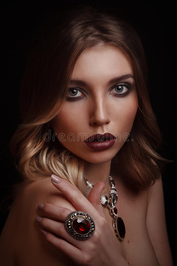 Studio beauty portrait of young woman wearing ring and necklace royalty free stock photography