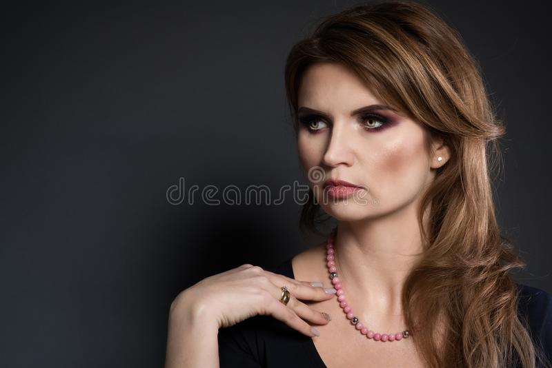 Studio beauty shot of woman with pink pearl necklace. stock image