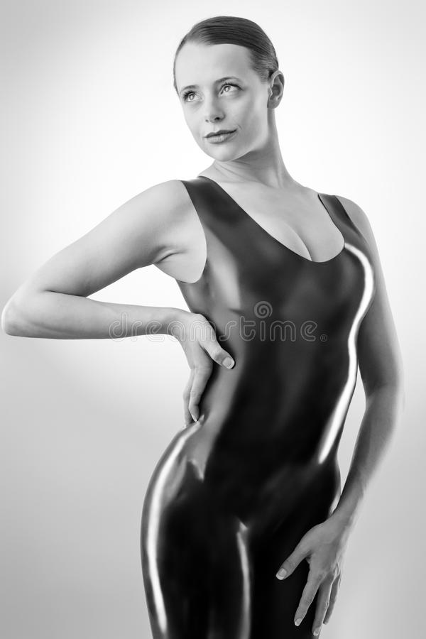 Woman in latex. Studio black and white image of young woman wearing latex royalty free stock images