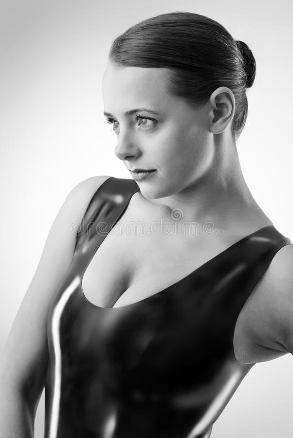 Woman in latex. Studio black and white image of young woman wearing latex royalty free stock photography