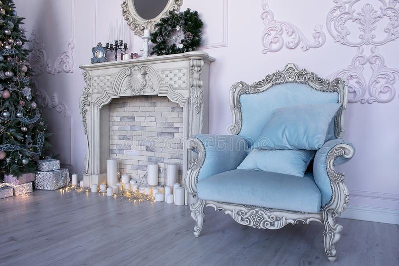 Studio with a blue armchair, a fireplace and a Christmas tree royalty free stock images