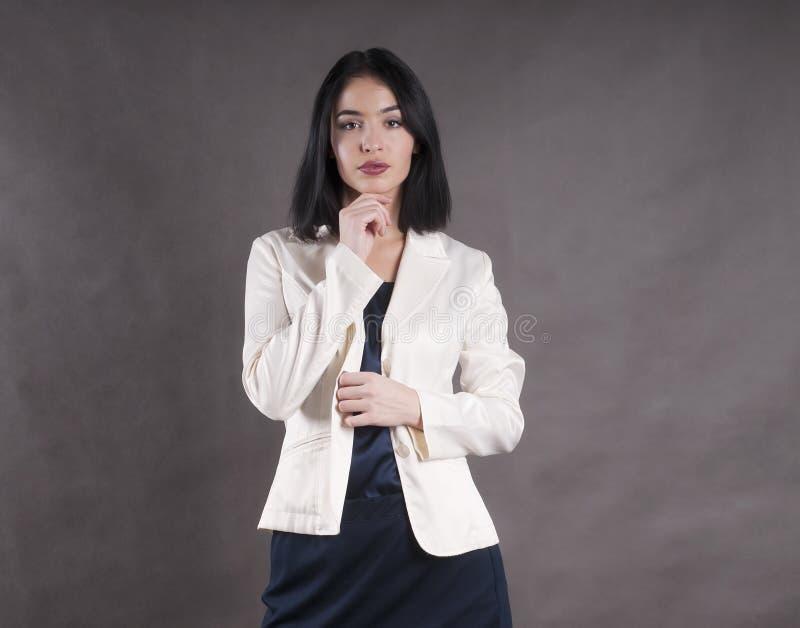 Studio castana della giovane bella di emozione del lavoro donna di affari seria del modello immagine stock