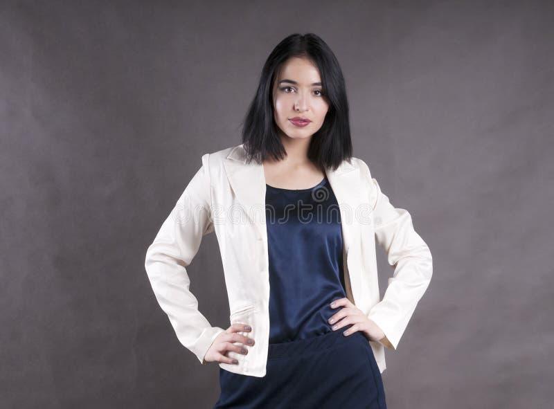 Studio castana della giovane bella di emozione dello standingwork donna di affari seria del modello fotografia stock