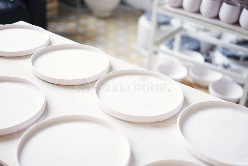 Studio ceramico, piatti bianchi piani dell'argilla pronti a lustrare e cottura fotografia stock