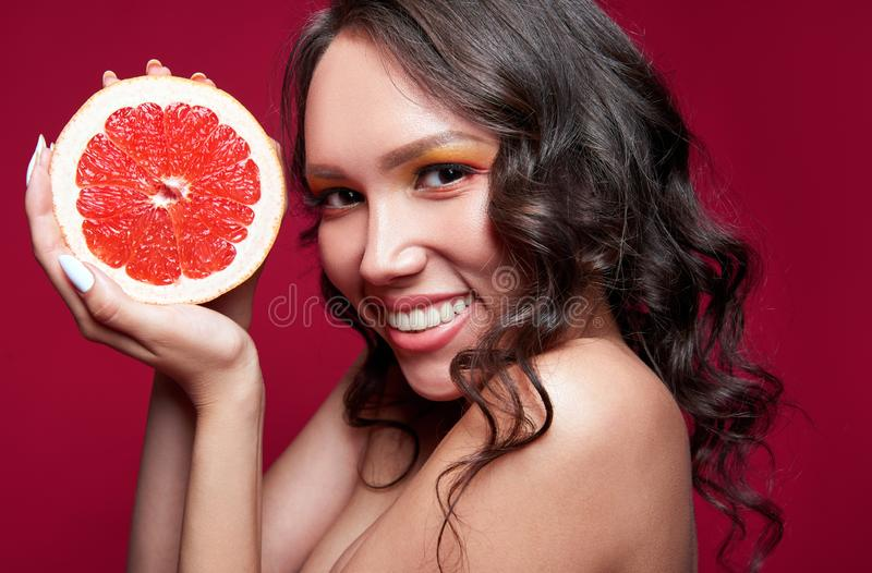 Studio close-up portrait of beautiful smiling young girl with slice of orange grapefruit in hands royalty free stock photos