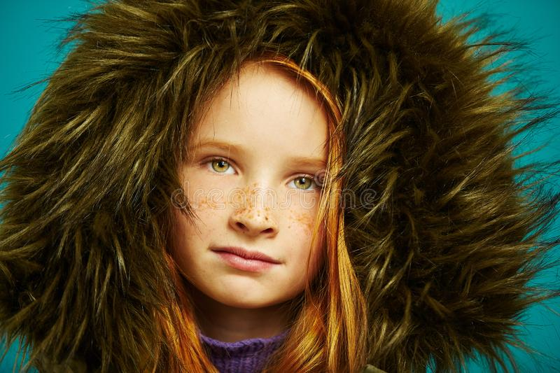 Studio close-up portrait of cute redheaded child girl with freckles hid in large hood jacket. stock image