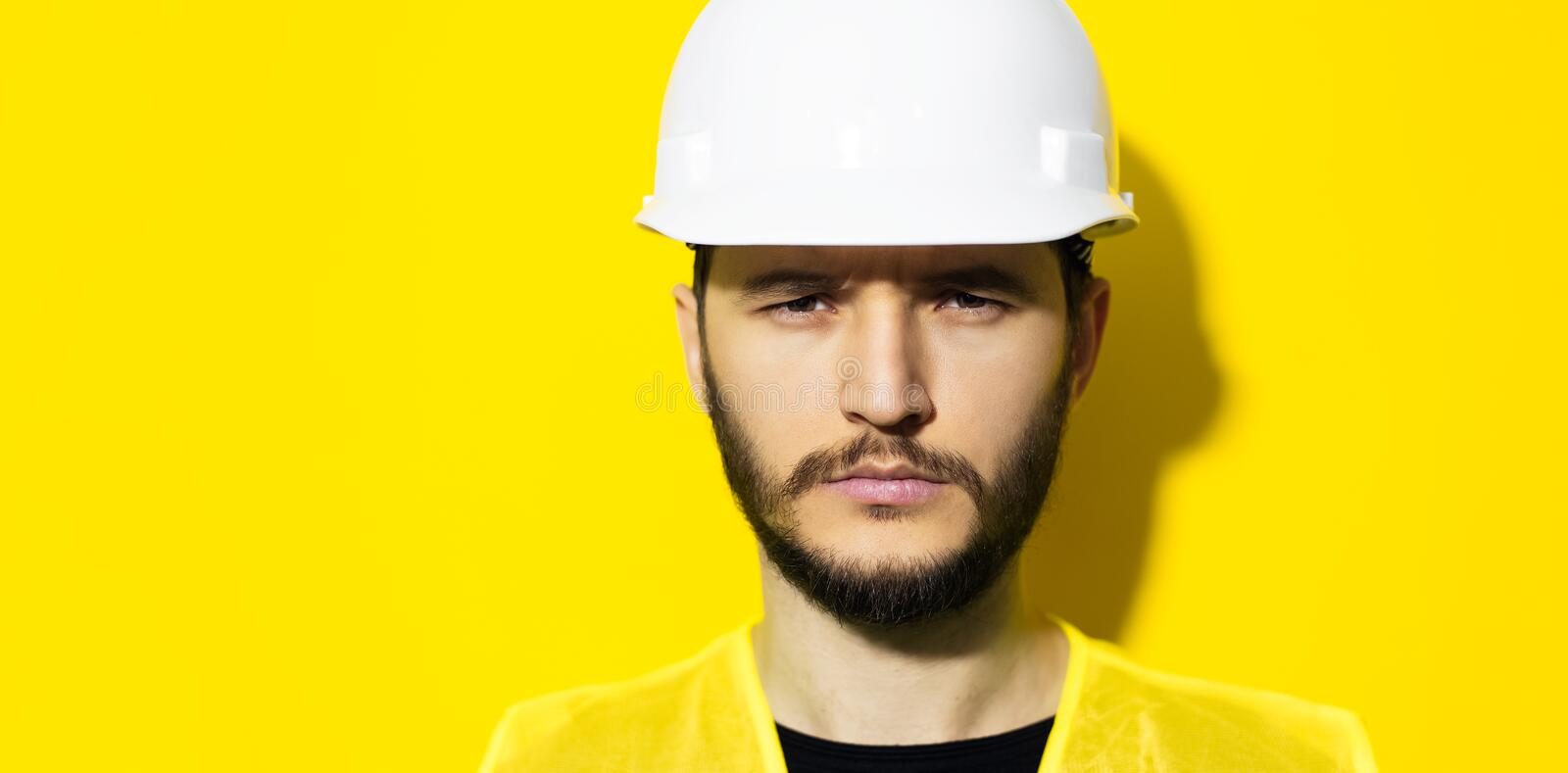 Studio close-up portrait of young serious man architect, builder engineer, wearing white construction safety helmet and yellow jac stock images