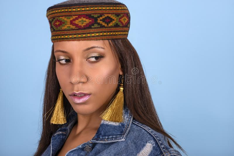 Studio close up shot of the young woman of the mulatta with make up wearing cap with east ornament and golden earrings royalty free stock photo