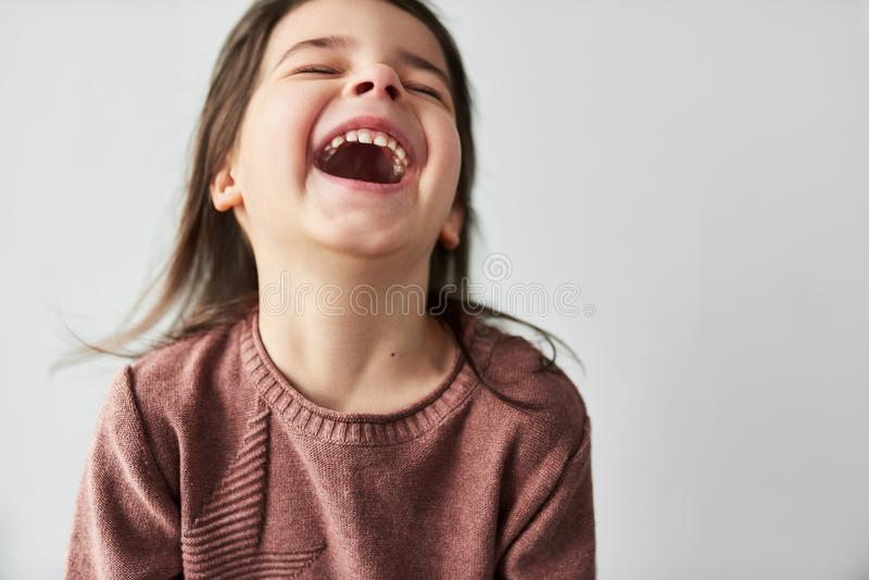 Studio closeup horizontal portrait of happy beautiful little girl smiling joyful and wearing sweater isolated on a white studio royalty free stock photos