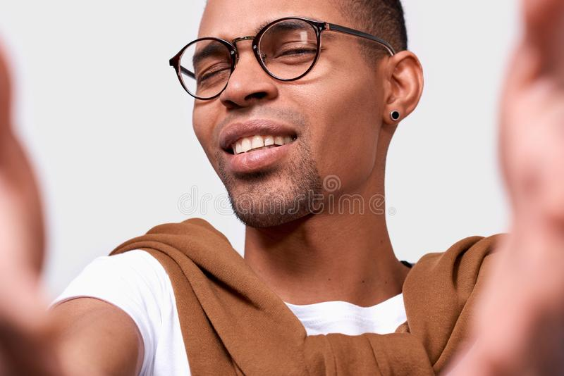 Closeup image of handsome African American young man smiling, wearing eyewear, looking at the camera and taking self portrait stock photos