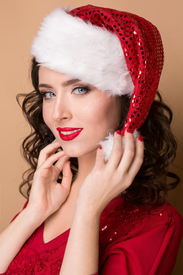 Studio closeup portrait of a beautiful girl in the hat of Santa Claus,. Studio closeup portrait of a beautiful girl with a red lipstick in the hat of Santa Claus stock image