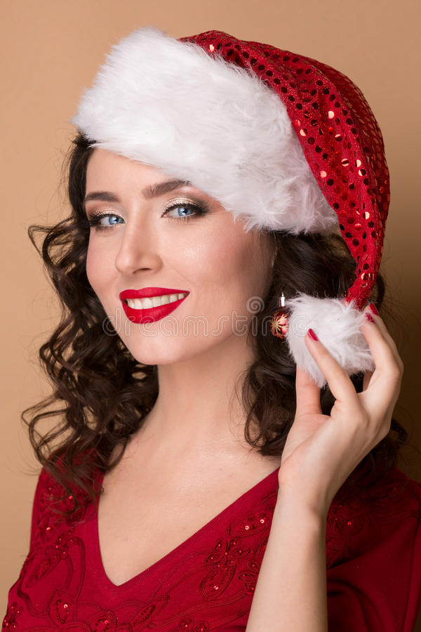 Studio closeup portrait of a beautiful girl in the hat of Santa Claus,. Studio closeup portrait of a beautiful girl with a red lipstick in the hat of Santa Claus stock photography
