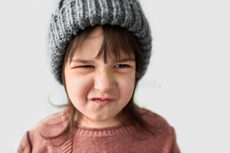 Studio closeup portrait of cute unhappy little girl with grumpy emotion in the winter warm gray hat, wearing sweater isolated on a royalty free stock photography
