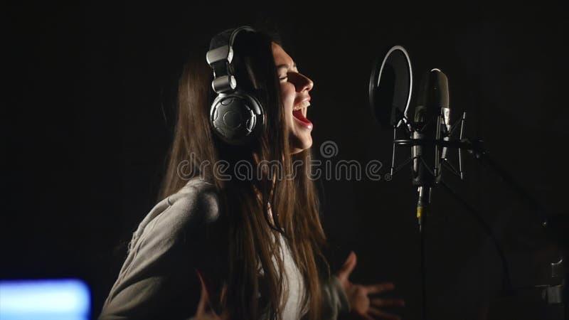 Studio d'enregistrement audio Femme avec des écouteurs et le chant de microphone de studio photo stock