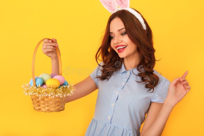 Studio della giovane donna isolato sulle orecchie d'uso gialle del coniglietto che tengono canestro che esamina le uova fotografie stock libere da diritti