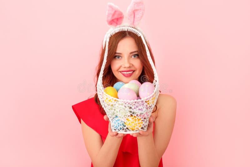 Studio der jungen Frau lokalisiert auf Rosa in einem roten Kleid und in Hasenohren, die Korb mit Eiern anbieten lizenzfreie stockfotos