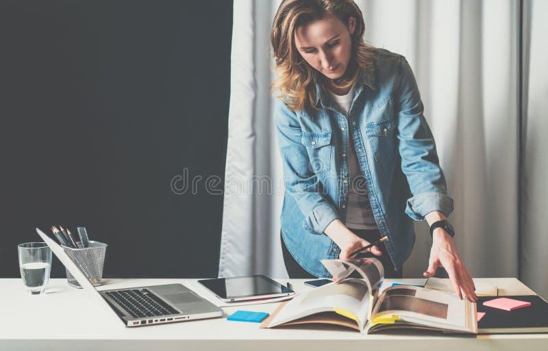 Studio di progettazione dell'ufficio, giovane donna di affari in camicia del denim che sta desktop vicino e che sfoglia catalogo immagini stock