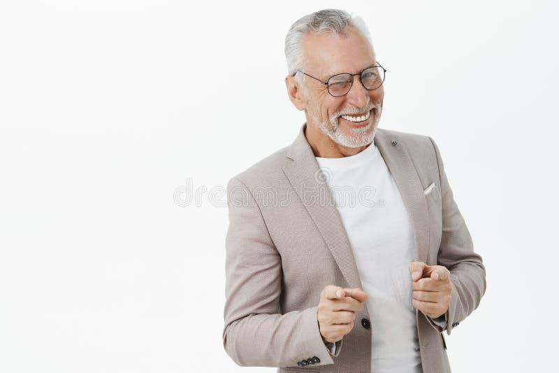 Studio di Unretouched sparato di incantare uomo d'affari maturo carismatico elegante e felice in vetri e vestito con i cattivi de fotografia stock