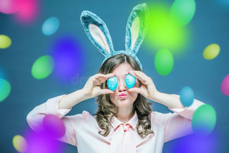 Studio die van een gelukkige jonge vrouw wordt geschoten die konijntjesoren dragen en een kleurrijk paasei voor haar oog steunen royalty-vrije stock foto