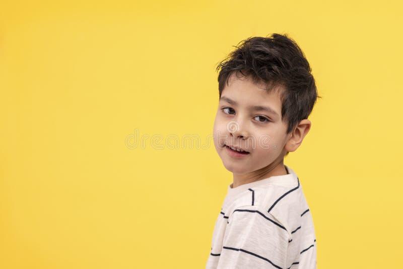 Studio die van een glimlachende jongen in een witte T-shirt op een gele achtergrond met exemplaarruimte wordt geschoten stock fotografie
