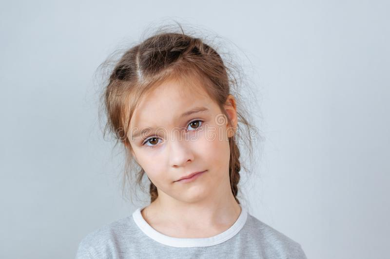 Studio emotional portrait of a serious little girl with long hair royalty free stock photo
