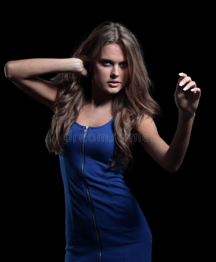 Beautiful woman in a blue dress posing on a black background royalty free stock photography