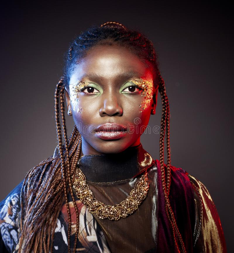 Studio fashion portrait of young African ethnicity woman with shiny make up stock image