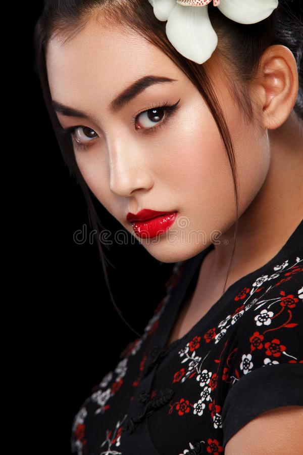 Studio fashion shot of Asian woman with white flower in hair stock photography