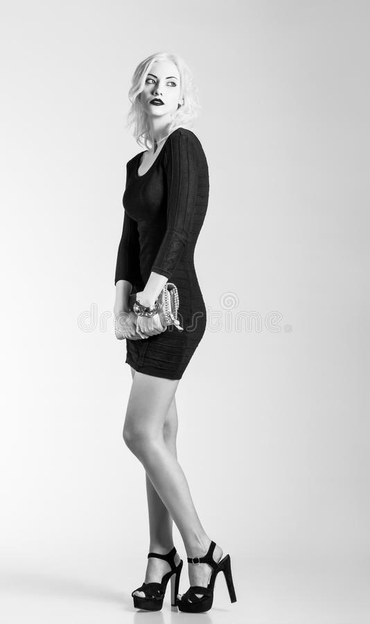Studio fashion shot: beautiful girl in black dress with clutch in hands. Black and white. Photo royalty free stock photos