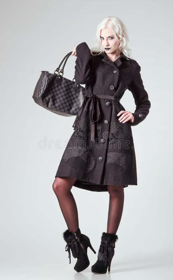 Free Studio Fashion Shot: Beautiful Girl In Black Coat And Boots, With Bag In Hand Stock Images - 35429734
